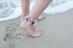 Walk on the beach. Female legs one bracelet ankle shells on the beach stock photo