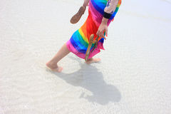 Walk on the beach. The girl wearing brightly colored clothes walking on the beach Stock Photo