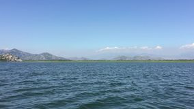 Walk by beautiful lake on boat. Summer day, Blue water. Huge Lake Skadar Montenegro. Largest lake in Montenegro. Trip by stock video