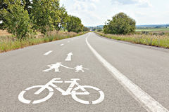 Walk and bike lane. Signs for bicycle and walking painted on the Royalty Free Stock Image