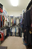Walk-in closet. Large fully stocked walk in closet with racks of clothing royalty free stock images