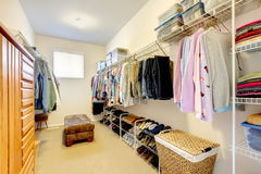 Walk-in closet. Big walk-in closet with shelves for clothes and shoes, dresser and wicker baskets stock photography