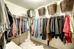Walk-in closet with clothes. On hangers and wicker baskets royalty free stock images