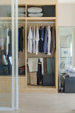 Walk in closet with clothes hanging in wooden wardrobe stock images