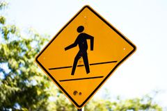 Walk or cross here sign in yellow with stick figure. Sign for crossing or walking path in yellow with black silhouette royalty free stock photo