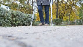 Walk on crutches on the road stock footage