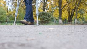 Walk on crutches on the road. Walking with crutches stock video footage