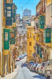 Living quarters of Valletta, Malta. Walk the descent in Old Mint street with a view on old residential buildings of native limestone with colorful wooden Maltese Royalty Free Stock Photo