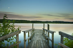 Walk the Dock. A dock leading to a large lake at sunset Stock Image