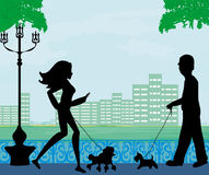 Walk the dog in a city park Royalty Free Stock Photography
