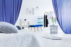 Walk-in dressing room. Stylish, walk-in dressing room with elegant clothes and blue fabric stock photography