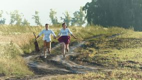 Walk in the field. A happy couple is running along the country road in the field. They are holding hands stock video