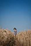 Walk in the field. Young beautiful girl walking down the road in a field Royalty Free Stock Image