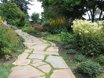 Walk Through the Flower Beds. A shale walkway winds through flowerbeds, toward a little building. Trees overhang the flowers and grass grows between the rocks on Royalty Free Stock Photo