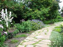 Walk Through the Flower Beds 2. A shale walkway winds through flowerbeds, toward a little building. Trees overhang the flowers and grass grows between the rocks Stock Photos