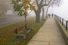 Walk on the foggy day. Two older people walk along the river which is hidden by thick autumn fog, after they rested on the bench royalty free stock image