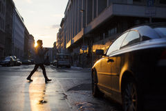 Walk. Germany, April 2013 - A woman walks on the street of western side of the Berlins city, during the sunset. Winter Stock Photography