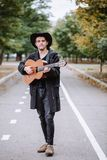 Walk with guitar in park. Vertical portrait young man who walk with guitar in park, play music and smile royalty free stock photography