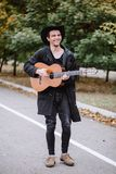 Walk with guitar. Photo young man who walk with guitar in park, play music and smile royalty free stock photo