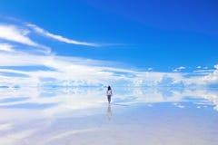 A Walk Into the Horizon. Female walks into the horizon at Salar de Uyuni, the Salt Flats in Bolivia royalty free stock photo