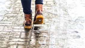 Walk on icy pavement. Walk on wet melted ice pavement. Back view on the feet of a man walking along the icy pavement. Pair of shoe on icy road in winter royalty free stock photo