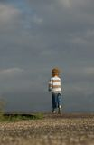 Walk of life. Photo of a little boy (2) walking away alone along a dike, against a dark clouded sky Royalty Free Stock Image