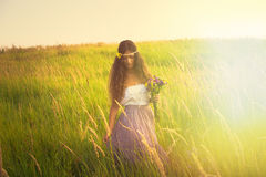 Walk in light. Young beautiful woman with long curly hair hold in hand a bouquet of wild flowers in romantic clothes walk in light at grass field Royalty Free Stock Image