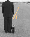 Walk the line. Business man standing in the middle of the road, facing towards the end of the road, in a black suit, with a briefcase, in the middle of the Stock Photo
