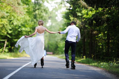 Walk of lovers on a garden. The wedding couple on rollers rolls on the road Royalty Free Stock Image