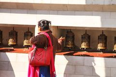 Walk of the Mantras. An elderly woman goes around the temple in a clockwise direction, turning the prayer wheels in the same direction, speaking her prayers stock image