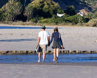 Walk With Me. Young couple strolling, holding hands on a Malibu, California beach Stock Photos