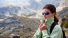 Walk in the mountains. Young female with sun glasses high in the mountains Stock Photo