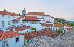 Walk in Obidos. The St James Church dominates over the tile roofs of old Obidos, surrounded by preserved ramparts, Portugal Royalty Free Stock Photos