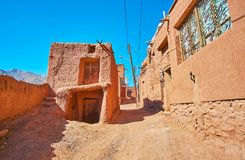 Walk the old hilly street, Abyaneh. Walk the old hilly street with adobe red-ochre houses, preserved since olden days in Karkas mountains, Abyaneh, Iran royalty free stock image