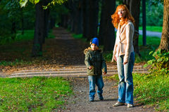 For a walk in the park. Young mother with bright red hair and her young son walk in the park Royalty Free Stock Images