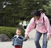 Walk in the park. Mom holding her sons hand as they walk in the park Stock Images