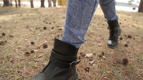 Walk in the park and legs in the frame. Footsteps on the ground in the woods stock footage