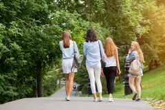Walk in the Park in summer. Four beautiful student girls walking and talking. stock photos