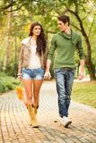 Walk In The Park. Young pretty girl with long legs in shorts and boots holding hands with her handsome boyfriend, walking trails in the park Royalty Free Stock Photo