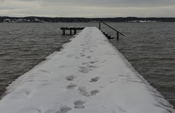 Walk on the pier. A pier on the Amersee in Germany with some tracks in the snow stock image