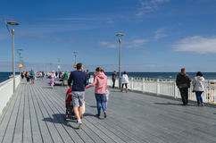 WALK ON THE PIER. KOLOBRZEG, WEST POMERANIAN / POLAND: Holiday guests of the resort walk the pier royalty free stock image