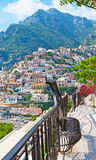 The walk in Positano. The pleasant walk along Cristoforo Colombo street, with amazing views on rocky mountains, old town on the slope, and colorful flowers royalty free stock image