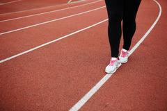Walk on racetrack. Legs of plus-sized woman walking down white line on stadium Royalty Free Stock Images