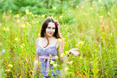 Walk after the rain. Beautiful girl in a field of flowers Stock Images