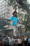 Walk on Rope-child labour in India. A young Indian girl is walking on a rope balancing with a series of pot on her head and holding a pole with both hands on Royalty Free Stock Photography