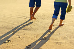 Walk on sand. Detail of the legs of a couple taking a walk in the sand Stock Image