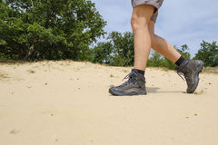 Walk through the sand with hiking shoes Stock Photography
