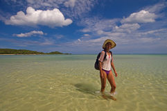 Walk on the shallow. The woman walks on the shallow of lagoon. She has a hat on her head Royalty Free Stock Photo