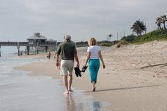 Walk the Shore. A husband and wife walk in the water's edge while strolling the Florida beach Royalty Free Stock Photography