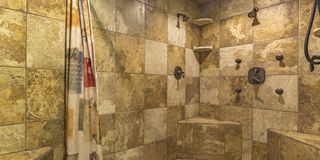 Walk in shower with brown tile wall and curtain stock images